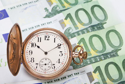Time is money concept with hundred euros bills and golden pocket watch.